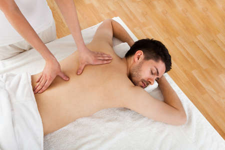 masaje deportivo: Hombre recibiendo masajes en el spa