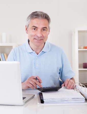 Portrait Of Happy Mature Man Calculating Finances Stock Photo - 20570139
