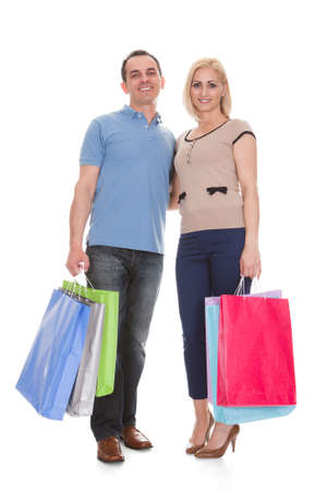 Young Couple Holding Shopping Bag Over White Background photo