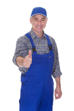 male's thumb: Mature Male Technician Making Thumbs Up Gesture Over White Background Stock Photo