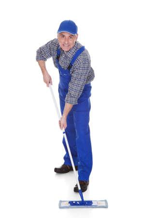 personal de limpieza: Hombre maduro limpieza de suelos con la fregona sobre el fondo blanco