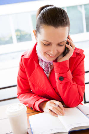 Happy woman looking at diary and talking on cell phone in restaurant photo