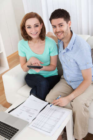 Portrait of young happy couple calculating budget