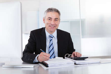 sitting at desk: Portrait Of Mature Businessman Calculating Finance At Office