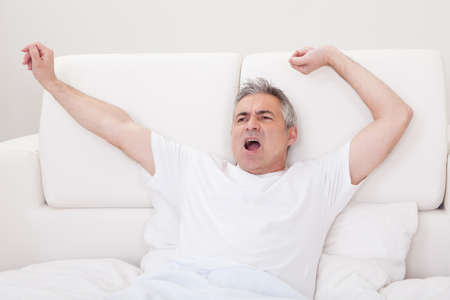 Portrait Of Yawning Mature Man Stretching His Arms In Bed photo
