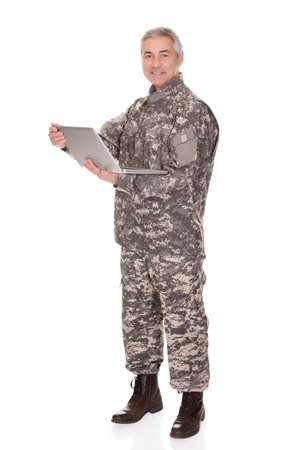 Mature Soldier Holding Laptop Isolated On White Background photo