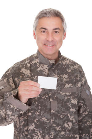 Mature Soldier Holding Blank Paper Isolated On White Background photo