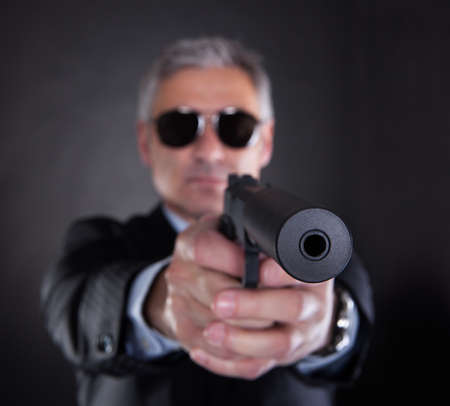silencer: Close-up Of Male With Handgun Over Black Background Stock Photo