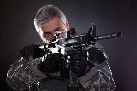 黒の背景上の銃を持つことを目指して成熟した兵士の肖像画