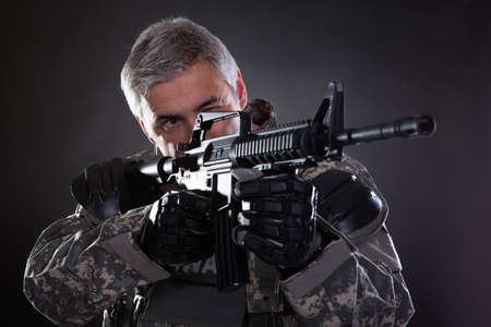 Portret Van Een Volwassen Soldaat met een pistool gericht Over Zwarte Achtergrond