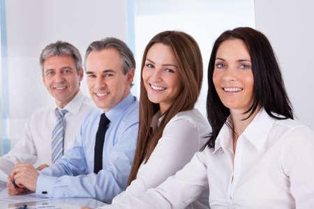 formacion empresarial: Retrato de empresarios felices que se sientan en una fila Foto de archivo