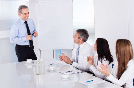 Group Of Business People Appreciating Businessman At Presentation photo