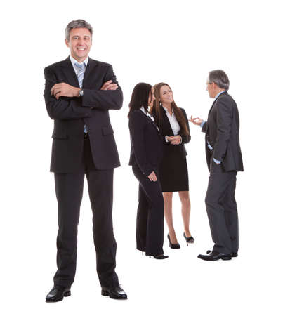 managers: Businessman Standing In Front Of His Colleagues Over White Background