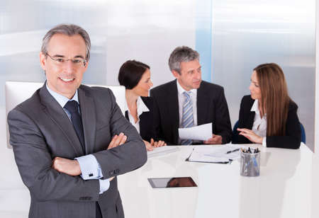 successful business woman: Happy Businessman Standing In Front Of His Colleagues In Office