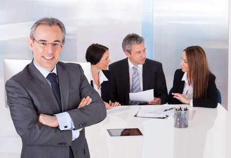 iş adamı: Office Onun arkadaşlarının önünde duran Mutlu İşadamı Stok Fotoğraf