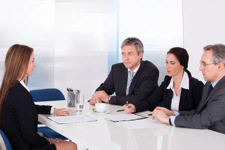 gespr�ch: Gruppe von Gesch�ftsleuten Interviewing Frau Im B�ro