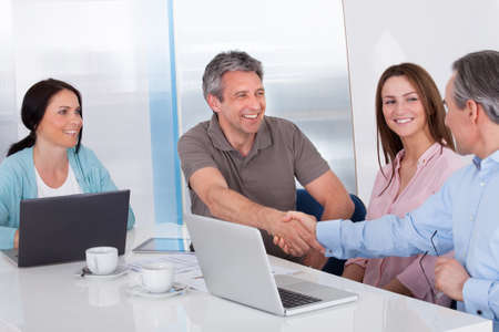 Two Businessman Shaking Hand In Front Of Colleague In Office photo