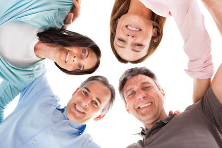 Group Of Happy People Making Huddle Over White Background photo