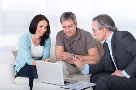 technology agreement: Happy Couple And Mature Consultant Discussing Together Stock Photo
