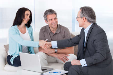 Portrait Of Mature Consultant Shaking Hand With Happy Woman photo
