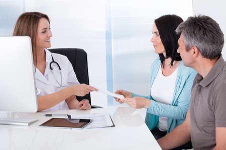 prestar atencion: Pareja feliz teniendo Card Dar del doctor