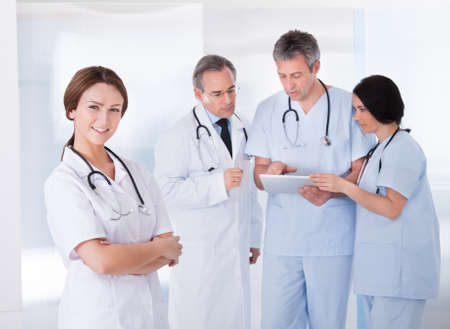 Female Doctor Standing In Front Of Team Using Digital Tablet photo