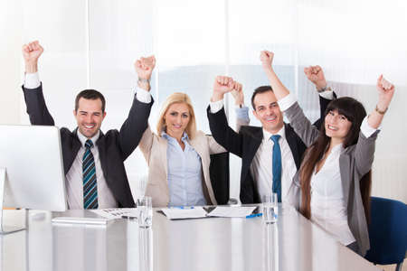 arms raised: Happy Business Team In Office Celebrating Success Stock Photo