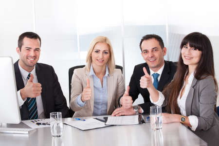 dedication: Happy Business Team Showing Thumb Up Sign Stock Photo
