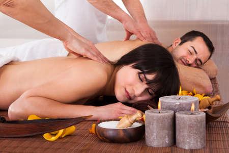 homme massage: Belle jeune couple appr?ciant le massage en spa Centre