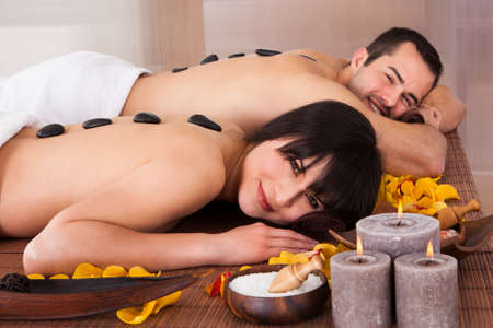 spa candles: Beautiful Young Couple Enjoying Hot Stone Therapy In Spa Centre