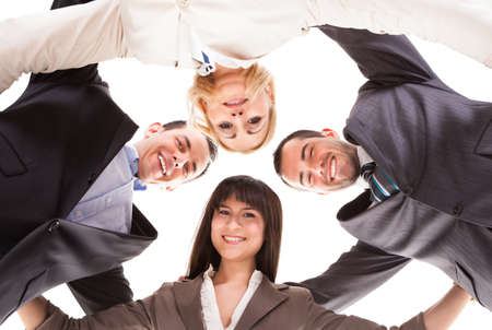 Portrait Of Happy Group Of Businesspeople Putting Heads Together Over White Background photo