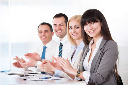 Happy Business People Clapping In The Office photo