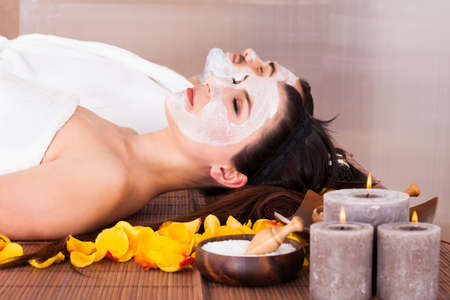 facial  spa: Couple With Face Mask In Spa Centre Stock Photo