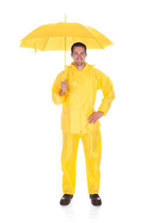 Mature Man Wearing Raincoat And Holding Umbrella Over White Background