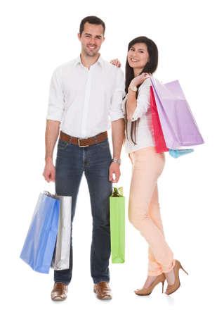 白い背景の上の若いカップル持株ショッピング バッグ 写真素材