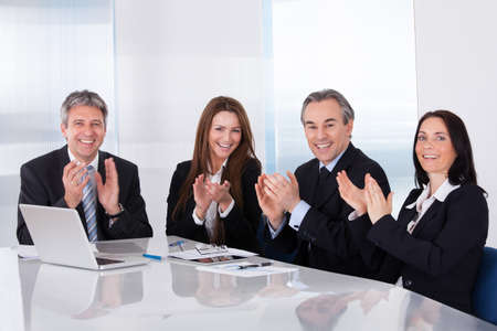 Portrait Of Happy Businesspeople Clapping In Office photo
