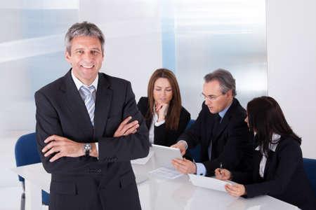 인식: 사무실에서 동료의 앞에 서있는 행복한 성숙한 사업가 스톡 사진