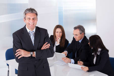 startup: Happy Mature Businessman Standing In Front Of Colleagues In Office