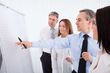 Group Of Businesspeople Discussing New Project On Whiteboard photo