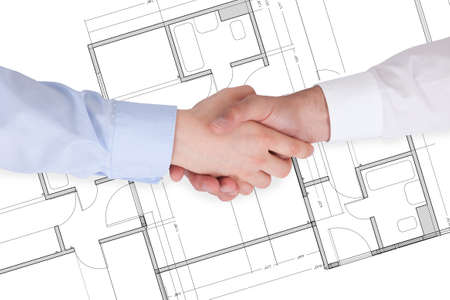 Close Up Of Two Businesspeople Shaking Hands Over Blueprint