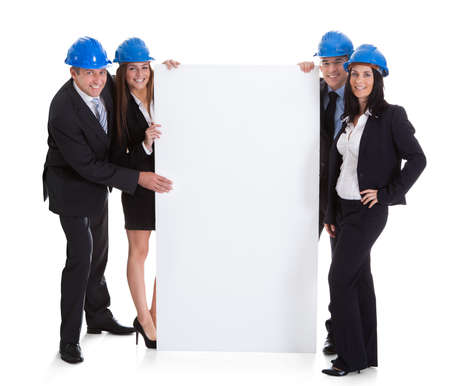 holding blank sign: Group Of Happy Architects Holding Blank Placard Over White Background Stock Photo