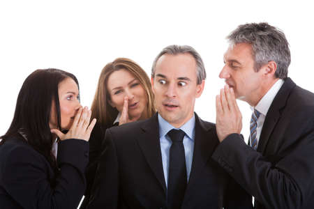 company secrets: Group Of Businesspeople Gossiping Over White Background Stock Photo