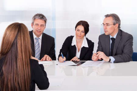 interviewing: Group Of Businesspeople Interviewing Woman In Office