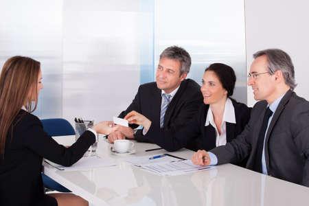 オフィスの同僚をビジネス カードを提供している実業家