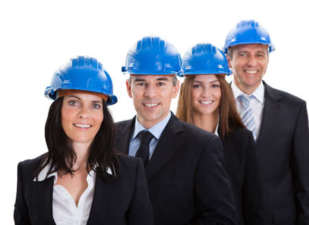 female construction worker: Group Of Happy Architects Standing In A Row Over White Background