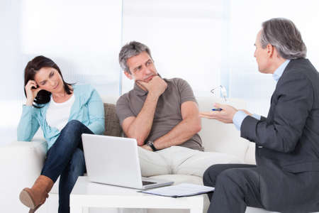 Mature Consultant Trying To Explain Worried Couple photo
