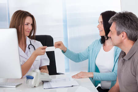 medical attention: Happy Couple Taking Giving Card From Doctor Stock Photo