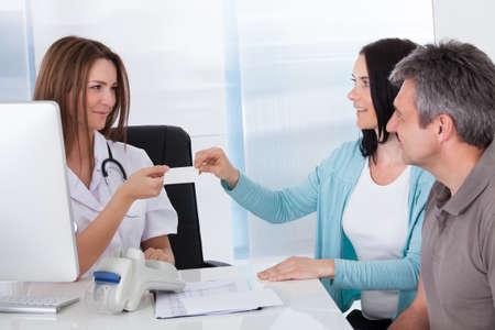 poner atencion: Pareja feliz teniendo Card Dar del doctor