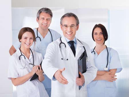 grupo de médicos: Hombre maduro médico ofreciendo apretón de manos delante de su colega Foto de archivo
