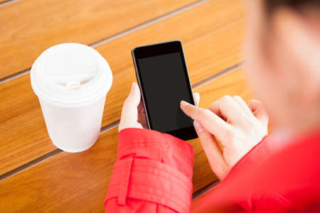Young woman using cell phone in restaurant photo